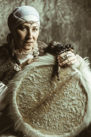 Elderly woman is a shaman playing a tambourine. Фото со стока - 106510829