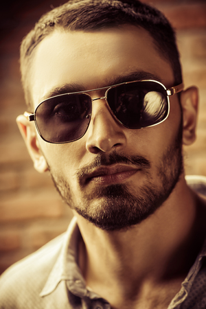 Close-up portrait of a handsome brunet man in sunglasses over brick wall background. Mens beauty, fashion. Mens barbershop, Hairstyle. Фото со стока