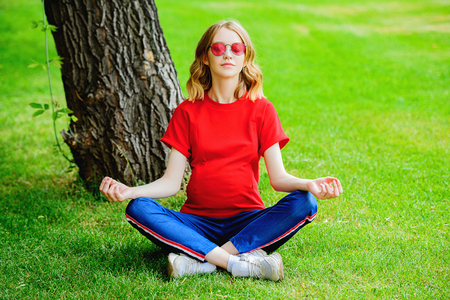 Young, pregnant woman doing yoga in the summer park. Pregnancy and motherhood. Healthy lifestyle. Yoga for pregnant women.