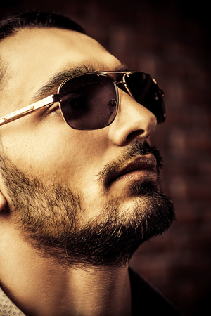 Close-up portrait of a handsome brunet man in sunglasses over brick wall background. Mens beauty, fashion. Mens barbershop, Hairstyle. 스톡 콘텐츠