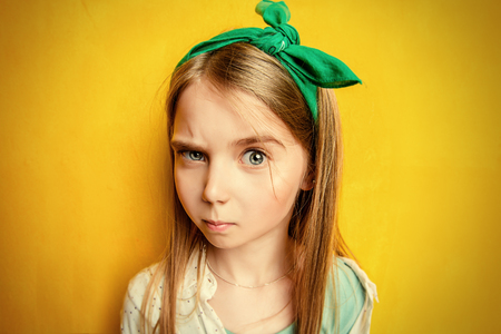 Close-up portrait of a funny emotional girl making faces at camera. Studio shot over yellow background. Childhood concept.