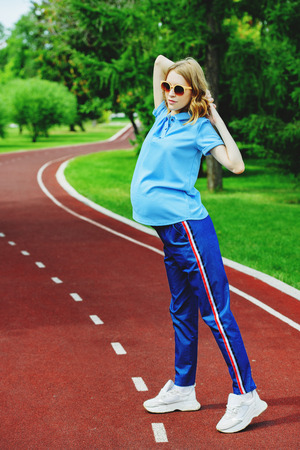 Pregnant woman doing exercises in the park. Pregnancy. Healthy lifestyle.