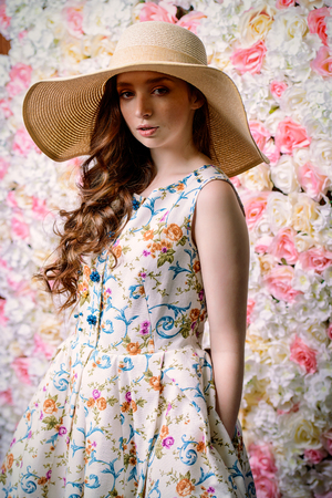 Portrait of a cute girl teenager wearing summer dress and hat by a floral background. Beauty, fashion.