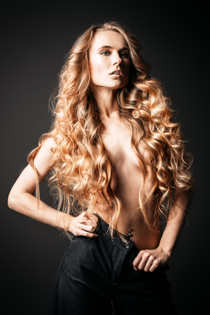 Portrait of a topless girl with long curly hair on a black background. Beauty, fashion. 스톡 콘텐츠