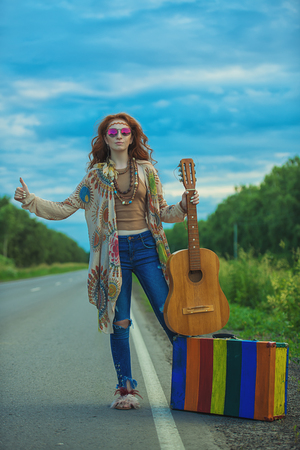 Hitchhiking girl. Beautiful hippie girl standing on a highway and catching a passing car. Spirit of freedom. Fashion shot. Bohemian, bo-ho style. Stock Photo