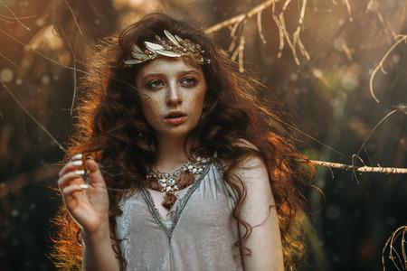Nahaufnahmeporträt eines rätselhaften schönen Mädchens, das in einem Wald aufwirft. Schönheit, Mode. Kosmetik und Make-up.