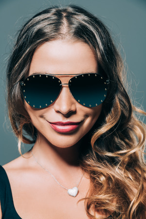An amazing woman has a charming smile. Sunglasses and optical collection. Elegant style.
