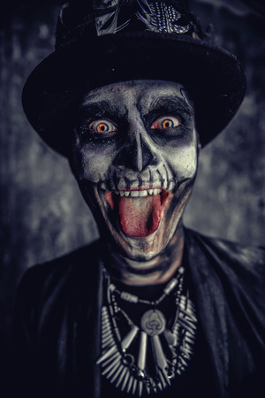 Close-up portrait of a man with a skull makeup dressed in a tail-coat and a top-hat. Baron Saturday. Baron Samedi. Dia de los muertos. Day of The Dead. Halloween.