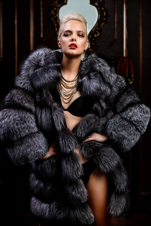 Portrait of a beautiful woman in luxurious fur coat posing in interior. Luxury, rich lifestyle. Fashion shot. Stock Photo