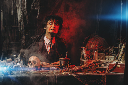 Portrait of a medieval scientist working in his laboratory. Alchemist. Halloween.