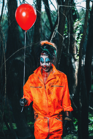 Scary man clown stained in blood in a night forest with a balloon. Male zombie clown. Halloween. Horror.