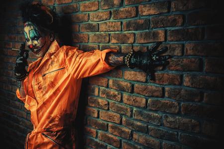 Halloween. Portrait of a bloodthirsty clown man over dark brick wall. Male zombie clown. Horror, thriller film. 스톡 콘텐츠