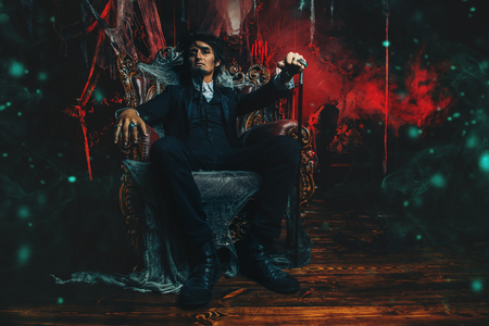 Halloween. Mysterious gloomy man in a black tailcoat in an old abandoned castle. The Dark Lord. Vampire man. Stock Photo