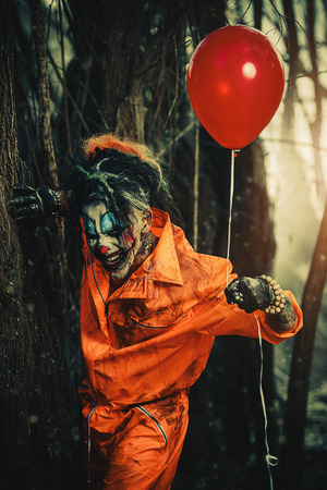 Scary man clown stained in blood in a night forest with a balloon. Male zombie clown. Halloween. Horror. Reklamní fotografie