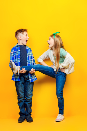 Childrens fashion. Beautiful  little children in casual outfits posing at studio over yellow background.