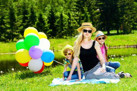 Happy summer day. Cheerful girls resting with their beloved mother in the park. Family concept. Banco de Imagens
