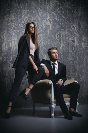 A photo of beautiful couple in studio. Classical suits. Men and women collection.