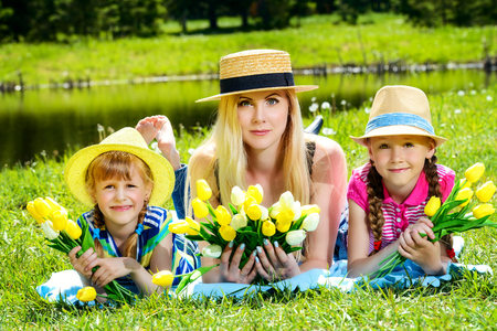 Cheerful girls with their beloved mother lying on a green lawn in the park. Summer holidays. Family concept. Banco de Imagens