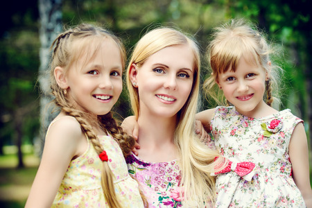 Portrait of a beautiful happy mother with her lovely daughters in the park. Summer holidays. Family concept. Banco de Imagens