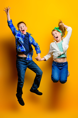 Childrens fashion. Beautiful  little children jumping at studio over yellow background.