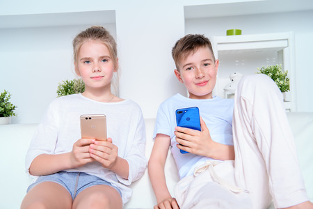 Two funny children spending time at home with smartphones. Free time, activity and hobby. Education. Family at home.
