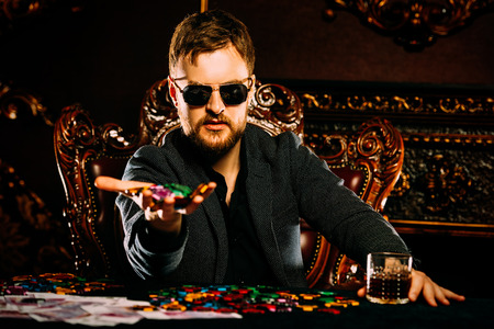 A wealthy mature man playing poker in a casino. Gambling, playing roulette. Rich and luxury.