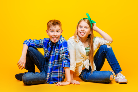 Portrait of two emotional children on a bright yellow background. Kid's fashion. 스톡 콘텐츠