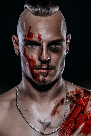 Fight club, MMA. Portrait of a bad guy fighter with a face in the blood, demonstrating his muscles and strength. Rocker, punk.