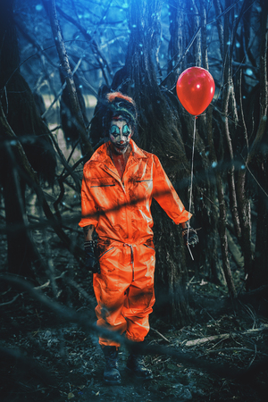 Scary man clown stained in blood in a night forest with a balloon. Male zombie clown. Halloween. Horror. Фото со стока