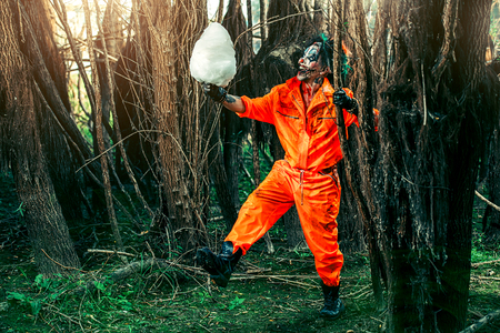 Bloodthirsty clown man in a night forest with a candy-floss. Halloween. Horror. Stock Photo - 107492271