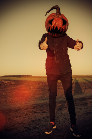 Full-length shot of a scary Jack-lantern with a pumpkin on his head. Halloween legend.
