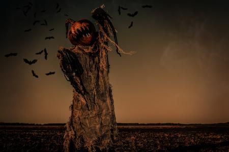 Leyenda de Halloween. Retrato de Jack-lantern con una calabaza en la cabeza de pie en el campo como un espantapájaros.