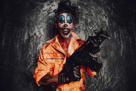 Crazy evil clown man stained in blood is smoking a cigar and holding a gun. Halloween. Horror, thriller film. Stock fotó - 108174224