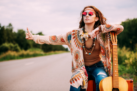 Hitchhiking girl. Beautiful hippie girl standing on a highway and catching a passing car. Spirit of freedom. Fashion shot. Bohemian, bo-ho style. Stockfoto