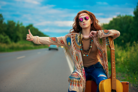 Hitchhiking girl. Beautiful hippie girl standing on a highway and catching a passing car. Spirit of freedom. Fashion shot. Bohemian, bo-ho style. 版權商用圖片