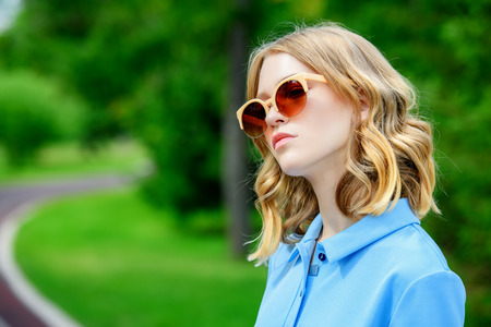 Portrait of a young woman walking in the park. Beautiful young lady in sunglasses. Healthy lifestyle. Imagens