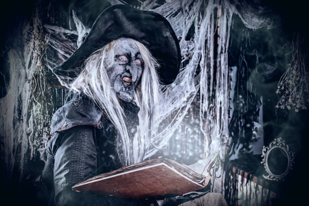 A witch checking the book with spells. Halloween. Horror movie. Stock Photo