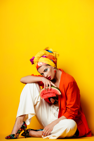 Portrait of a fashionable woman with watermelon and bright make-up. Yellow background. Beauty, fashion, make-up concept. Stock Photo
