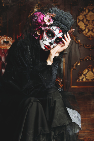 Calavera Catrina in black dress in interior. Sugar skull makeup. Dia de los muertos. Day of The Dead. Halloween.