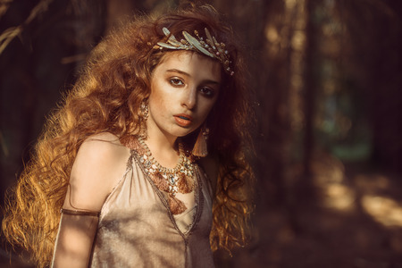 Portrait of a enigmatic beautiful girl posing in a forest. Beauty, fashion. Cosmetics and makeup. Reklamní fotografie - 107809390