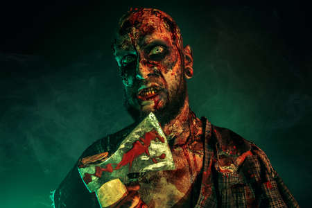 Close up of a scary zombie with an axe. Halloween. Horror film.