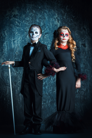 Portrait of children in costumes of Calavera Catrina and skeleton. Halloween carnival. Dia de los muertos. The Day of the Dead. Stock Photo
