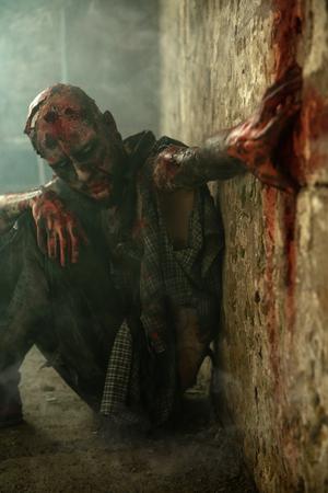 Creepy scary zombie sitting on the floor. Halloween. Horror film.