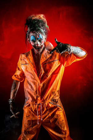 Frightful clown man spattered with blood is smoking a cigar. Bloody red background. Halloween. Horror, thriller film. Stock Photo