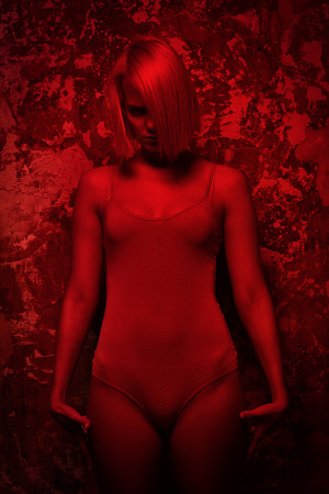 Attractive young woman in flesh-colored bodysuit posing in studio in red light. Beauty, fashion. Stock Photo