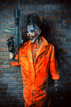 Crazy evil clown man stained in blood is holding a gun. Halloween. Horror, thriller film. 스톡 콘텐츠