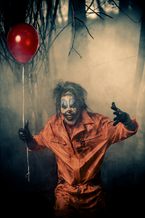 Scary man clown stained in blood in a night forest with a balloon. Male zombie clown. Halloween. Horror. Archivio Fotografico - 108314701