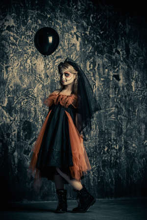 A girl in halloween carnival costume is standing by a grunge wall with black balloon. Happy Halloween!