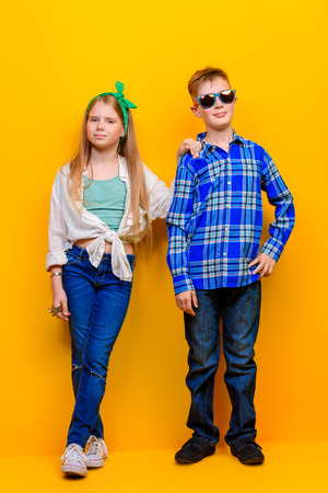 Childrens fashion. Beautiful  little children posing at studio over yellow background. Laughing and happy.