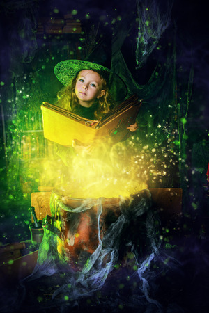 Happy Halloween. Cute child girl in witch costume is in a witchs lair. Cute cheerful little witch reads a spellbook and cooks a magic potion.